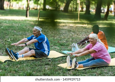 selective focus of senior woman with grey hair and multicultural men working out on fintess mats