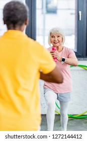 selective focus of senior woman with smartwatch doing exercise with dumbbell at gym