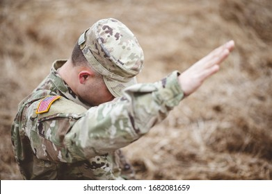 A selective focus shot of an American soldier with his hand raised above