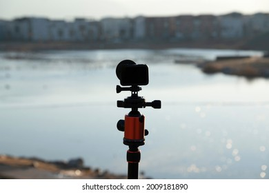 Selective focus of a silhoutte of 4k camera on a tripod