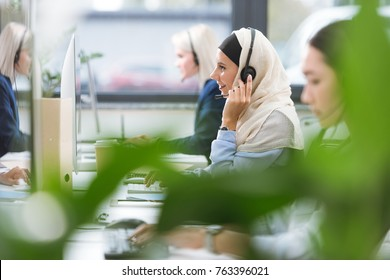 selective focus of smiling arabic call center operator in hijab in headset working on computer at workplace in office