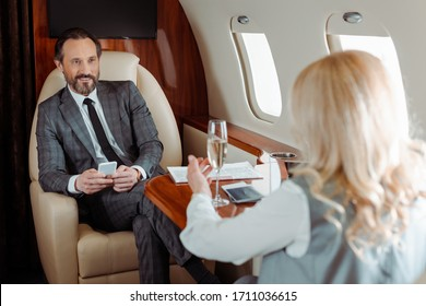 Selective focus of smiling businessman with smartphone looking at businesswoman with champagne in plane