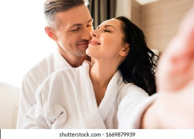 selective focus of smiling girlfriend taking selfie with boyfriend and kissing in hotel