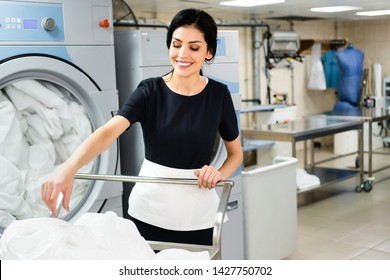 selective focus of smiling housemaid near basket with white bed sheets