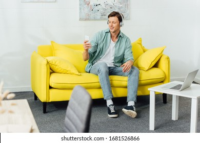 Selective focus of smiling man in headphones using smartphone on couch near laptop on coffee table