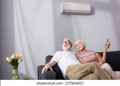 Selective focus of smiling senior woman holding remote controller of air conditioner near husband at home