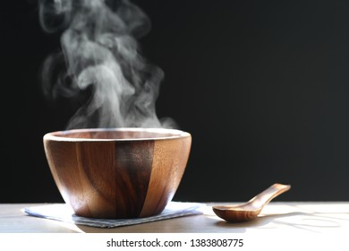 Selective focus of smoke rising with hot soup in cup on dark background