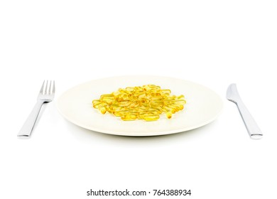 Selective focus of soft yellow capsules with healthy omega 3 fish oil on a dinner plate with knife and fork.