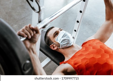 selective focus of sportsman in medical mask exercising with barbell in gym