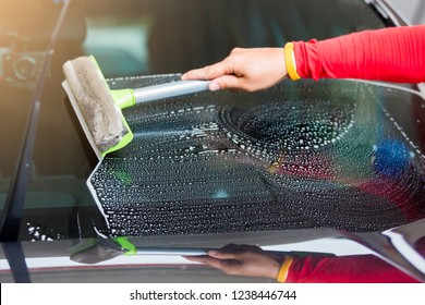 Selective focus to staff using squeegee and liquid car wash to clean the windshield. Car service in gas station.