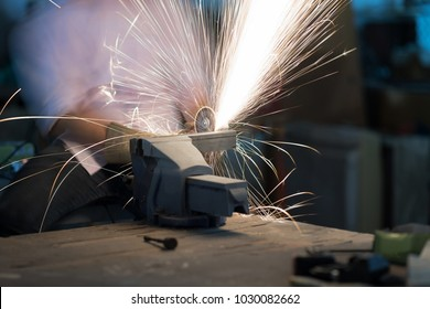Selective focus at steel rod and motion Blurred. Man use electric Steel cutter and clamp metal in factory and throwing many sharp sparks. industry in construction site concept.