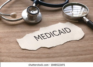 Selective focus of stethoscope, magnifying glass and piece of paper written with Medicaid on wooden background.