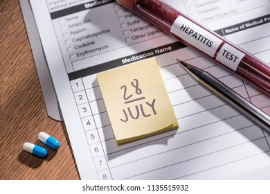 selective focus of stick it 28th july date, medical questionary, pills and test flask with lettering hepatitis test on table