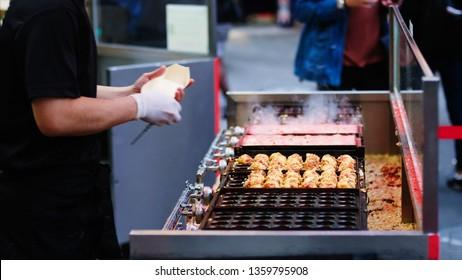 Selective focus street food of Octopus meat balls called Takoyaki on hot pan. Takoyaki is a most famous Japanese snack food in Japan.