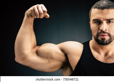 selective focus of strong man showing muscles isolated on black