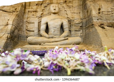 (Selective focus) Stunning view of the beautiful Samadhi statue carved in stone with blurred flowers in the foreground. The Samadhi Statue is situated at Mahamevnawa Park in Anuradhapura, Sri Lanka.