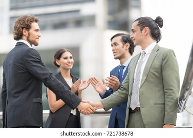 In selective focus of Successful businessmen handshaking after good deal against cityscapt building center blurry background.Business partnership meeting concept.