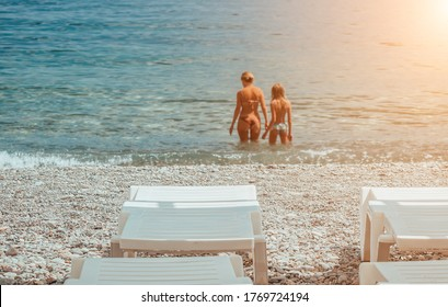 Selective focus. Summer vacation destination. white sunbeds on the rocky beach with mother and daughter going to the sea in background. Vacation And Tourism Concept. Sunbeds On The Paradise Beach.