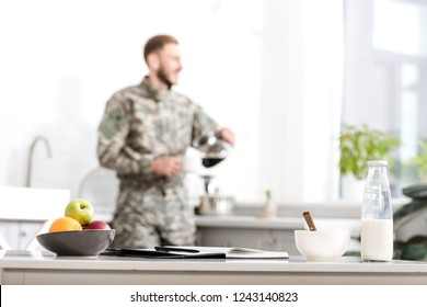 Selective focus of table with fruit bowl, milk bottle, notebook and pen, army soldier pouring filtered coffee in kitchen on background