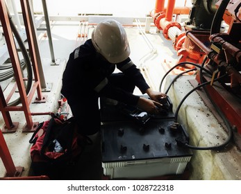 Selective focus of the technician is checking the condition of the battery by battery tester.