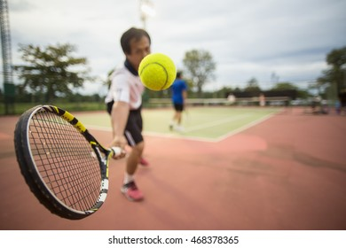 Selective focus of tennis forehand slice from baseline of outdoor court