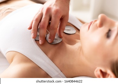 Selective focus of therapist setting electrode on chest of patient during electrode treatment