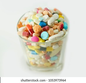 selective focus of top view of drug in form of tablet , capsules in glass on white background
