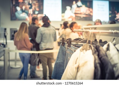 Selective focus trending clothes hanging at clothing shop with blurred long queue of customer behind stanchion beltline at checkout counter