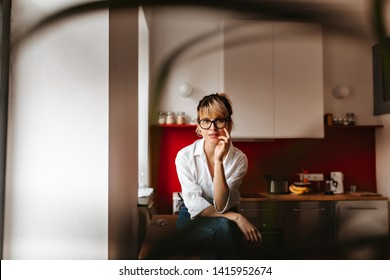 Selective focus of trendy girl sitting on table. Dreamy european lady posing at home in morning.
