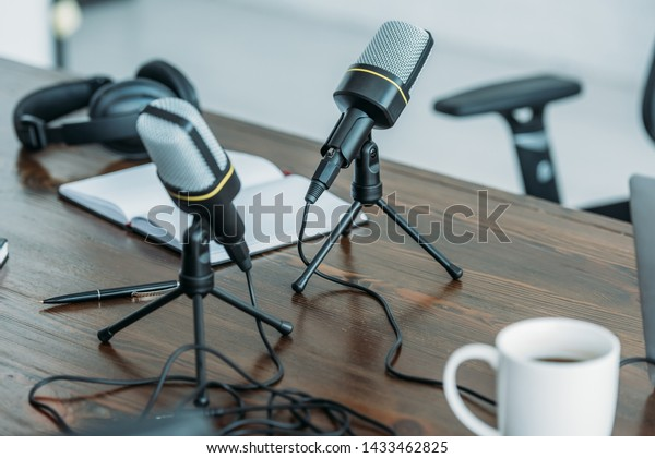 selective focus of two microphones om wooden table in broadcasting studio