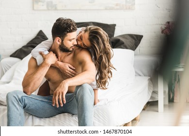 selective focus of two people in love hugging while sitting in bed