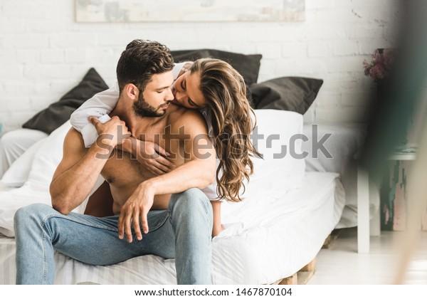 2人の人がベッドに座りながらハグをすることの限定フォーカス