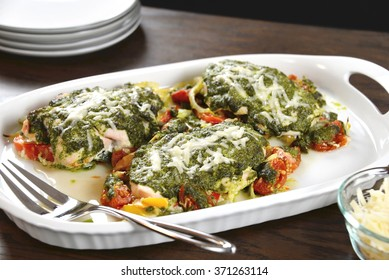 Selective focus was used on these tasty baked chicken breasts which are covered with basil pesto sauce, fresh cherry tomatoes, yellow bell peppers and topped with melted parmesan cheese.