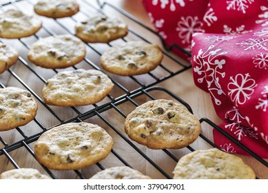 Selective focus was used on these freshly baked homemade chocolate chip cookies that have been placed on baking racks to cool off before storing.  A winter holiday towel with snowflakes is on the side