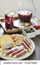 Selective focus was used on this tall glass of refreshing fruit filled red sangria and accompanying tray of cheese and crackers and other delicious hors Dâ??oeuvres.