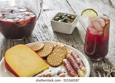 Selective focus was used on this glass of refreshing red sangria made with a variety of healthy fresh fruit.  It is served with appetizers on a rustic weathered wood background.