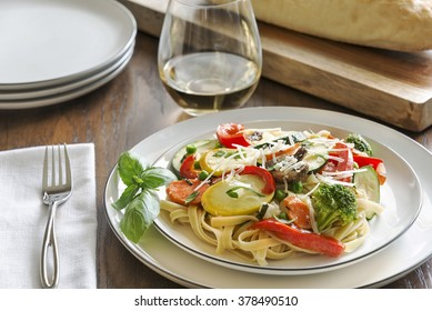 Selective focus was used on this pasta primavera made with fettuccine, basil, squash, zucchini, red bell pepper, broccoli, carrots, mushrooms and peas and topped with freshly shredded parmesan cheese.