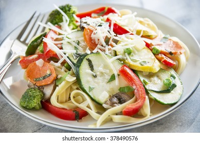Selective focus was used on this plate of pasta primavera with fettuccine, basil, squash, zucchini, red bell pepper, broccoli, carrots, mushrooms and peas and topped with shredded parmesan cheese.