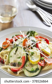 Selective focus was used on this pasta primavera made with fettuccine, squash, zucchini, red bell pepper, carrots, basil, peas, mushrooms and broccoli and topped with freshly grated parmesan cheese.