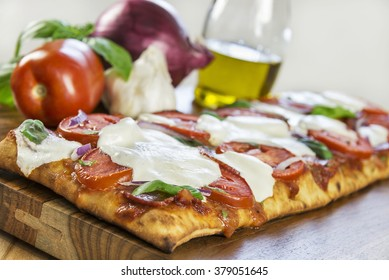 Selective focus was used on this hot, fresh grilled rustic crust pizza topped with Roma tomatoes, fresh mozzarella, Italian salami, basil and red onion.