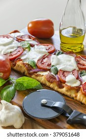 Selective focus was used on this hot, fresh grilled rustic crust pizza topped with Roma tomatoes, fresh mozzarella, Italian salami, basil and red onion. Room for copy space on the top left.