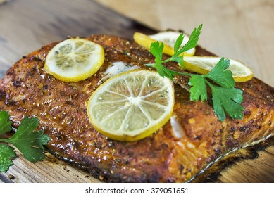 Selective focus was used on this piece of healthy grilled cedar plank salmon that has been garnished with sliced lemon and parsley.