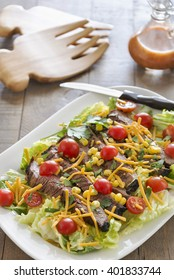 Selective focus was used on this healthy romaine lettuce salad that is topped with grilled steak, corn, cherry tomatoes, cilantro and shredded cheddar.