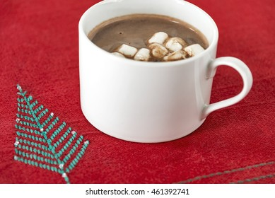 Selective focus was used on this holiday image of a cup of hot chocolate on a Christmas placemat