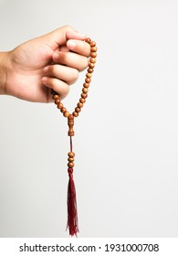 Selective focus vertical image hand of muslim woman holding a prayer beads isolated on white background with copy space.