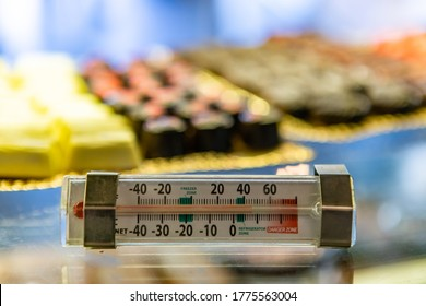 selective focus view of Fahrenheit mercury thermometer on a patisserie refrigerator, with freezing, refrigerating and warm danger zones Indications.