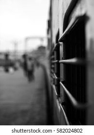 Selective focus view of the outside of a train carriage in black and white, at an Indian train station.