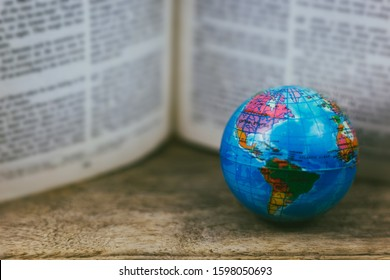 selective focus vintage globe with open Bible, a missions concept.