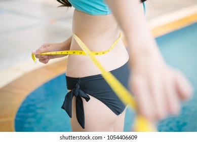 Selective focus waistline  woman. Weight loss, slim body healthy lifestyle concept. Fit fitness girl measuring her waistline with measure tape on swimming pool background.