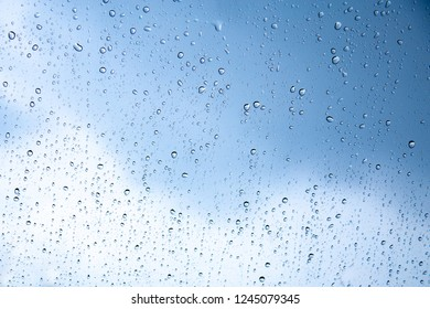Selective focus of the water drops on glass with overcast sky from the storm.Rain drops on the glass with overcast sky in the rainy season. Can use for add text and abstract background.